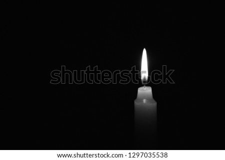Light candle burning brightly in the black background. Candle flame. There's room for your text. Black and white photo. The concept of mourning, grief or sorrow. Located on the right side of the shot.