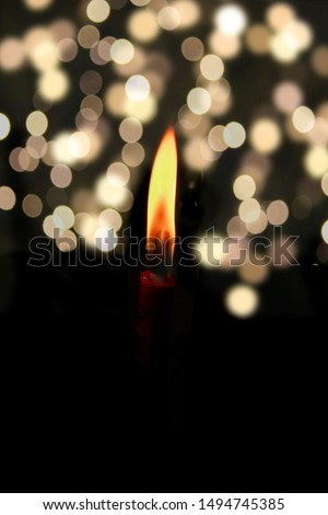 light candle burning brightly with bright bokeh in the black background,light in the shadow. #1494745385
