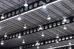 light ceiling and nature sunlight in warehouse. light bulb of exhibition hall hang under the metal roof. airy interior design of gym and stadium.  bright office industrial construction building.
