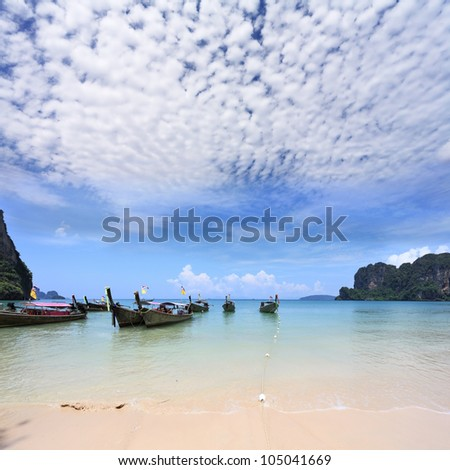 Light cirrus clouds over the warm sea. Picturesque native boat Longtail waiting on the beach the first tourists