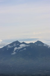 Light clouds around the mountain. Big blue mountain under the grey sky. Mount Gede or Gunung Gede is a stratovolcano tropical mountain located in Bogor, West Java, Indonesia. Holiday destination