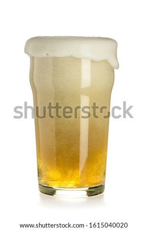 Light cold beer in a nonic-pint glass with a thick cap of rising foam and overflowing, isolated on a white background. Vertical image. Stock photo ©