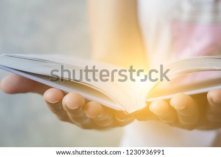 Light coming from book in woman's hands in gesture of giving, offering. Concept of wisdom, religion, reading, imagination. #1230936991