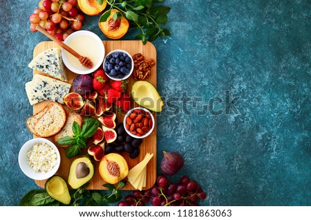 Light delicious fruit and cheese and nuts plateu, easy party snack or healthy lunch, view from above #1181863063