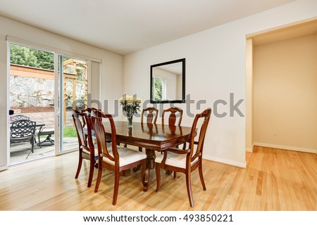 Light dining room interior with wooden carved table and chair set. Opened sliding door lead out to the back yard. Northwest, USA #493850221