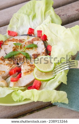 Light dinner- grilled swordfish with fresh salad leaves and vegetables. Close up