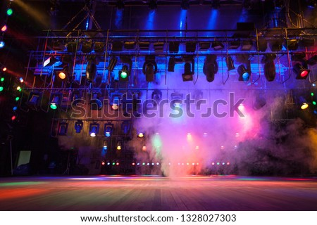 Light effects on stage created with theatrical lighting equipment and a smoke machine #1328027303