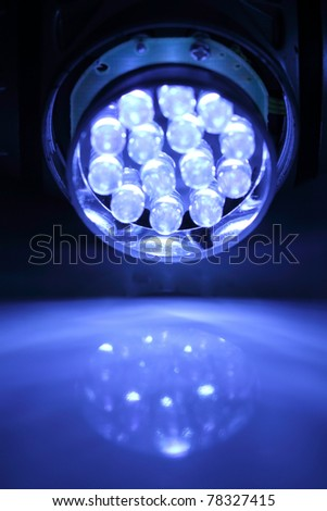 Light-emitting diode flashlight turned on against a blue background.