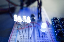 Light-emitting diodes on breadboard electrical panel. Close-up of blue led, shining on engineer workplace. Electrician-inventor laboratory