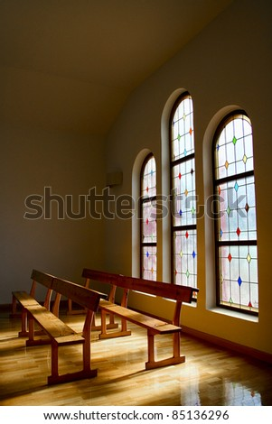 Light entering a church by a glass window colors, shining on the floor and wooden benches