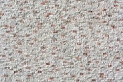 light facture background of orange and white small stonework, masonry. Building urban facade design
