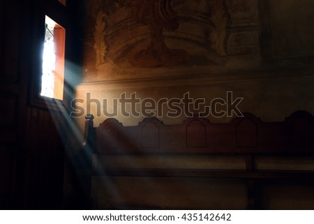 light falling through window in old church on wooden bench, peaceful moment