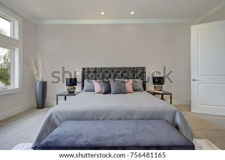 Light filled bedroom showcases a king size bed with tufted headboard dressed in grey bedding and a dark blue velvet bench placed on a white fluffy rug. Northwest, USA #756481165