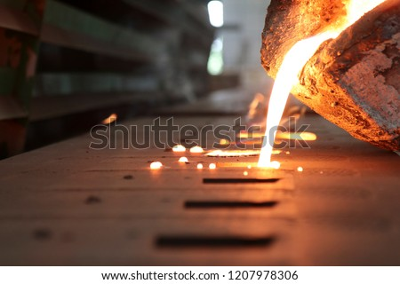 Light from high temperature Iron molten metal pouring in green sand mold ;Foundry process to manufacture cast product for automotive and electrical; industrial engineering metallurgy background ,