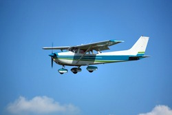 Light general aviation cessna aircraft on final with cloud sky landing configuration