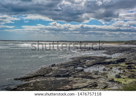 Light glistening on the sea with rocks in the foreground and a moody sky