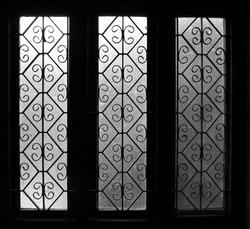 light gradient on three translucent glasses of identical windows with vintage designs symmetric pattern