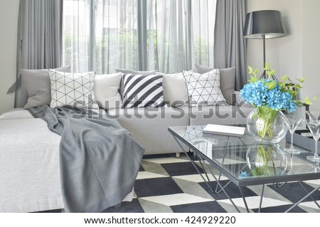 Light gray L shape sofa set with varies pattern and color pillows in modern living room