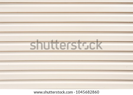 Light gray (white) vinyl wooden siding panel background with imitation wood texture. Vinyl siding texture and background in residential neighborhood housing. Real estate background concept.