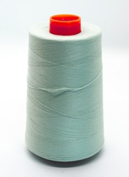 Light green bobbin thread isolated on white background. Close up of a spool of green sewing thread. Thread is a type of yarn but similarly used for sewing. Made of cotton, wool, linen, nylon, and silk