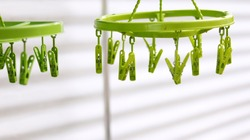 Light green plastic clothespins, green clip clothes on the hangers, use for hanging clothes or underwear after washing and drying. Thailand useful object style, isolated in white zinc blur background.