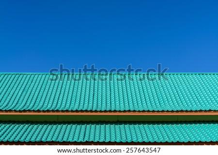 Light green roof tile pattern over blue sky