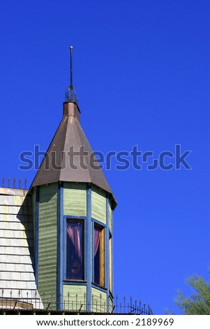 Light green Victorian turret with a lightning rod is presented against a brilliant blue desert sky