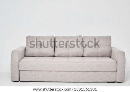 Light grey classic sofa with three pillows isolated at white background