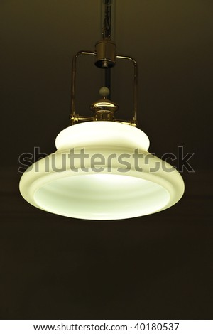 Light hanging from ceiling with the light on in a dark room
