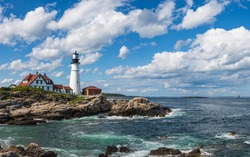 Light house on a rocky sea coast with blue sky backdrop with clouds