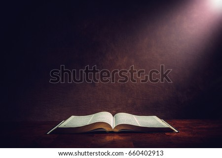 Light illuminating the Holy Bible on a wooded table.