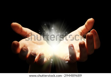 Light in the human hands in the dark