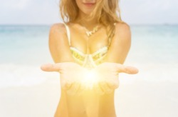 light in the palm of the hands. Defocused image.beautiful blurred girl open the hands and reveals light in between