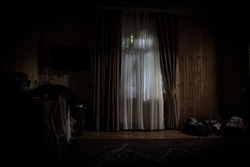 Light in window with curtain inside bedroom at night. Horror scene. Halloween concept. Blurred silhouette of ghost