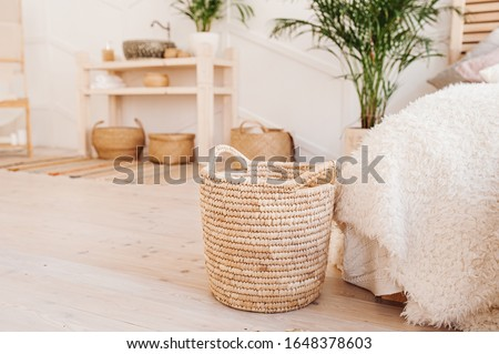 Light interior made of natural eco components. Wicker straw basket for storing clothes and things on the background of the washbasin and bath in the Boho style with wicker baskets and wooden shelves