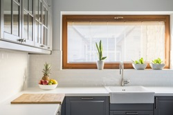 Light kitchen with white countertop, sink, window and grey furniture