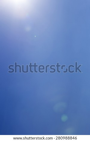 Light leak and a lens flare from the sun over clear blue sky with copy space