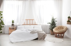 Light modern room interior with comfortable bed