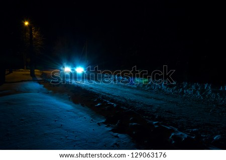 Light of car headlights inundates a nightly snow bound road.