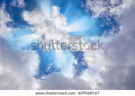 Light or sun rays bursting from the clouds in shape of a cross #609068567