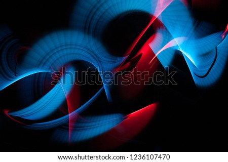 Light painting abstract background. Blue and red light painting photography, long exposure, ripples and swirl against a black background.