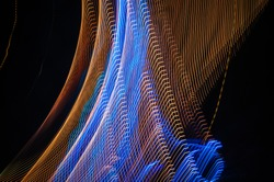 Light painting abstract background. Orange and blue light painting photography, long exposure, ripples and swirl against a black background.