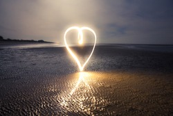 Light Painting Art: Heart painted with light into darkness on the beach at night