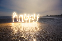 Light Painting Art: Writing happy with light into darkness at a romantic night on the beach