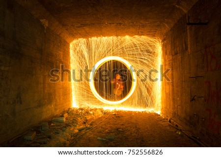 Stock Photo Light painting / light drawing with fire and steel wool underground