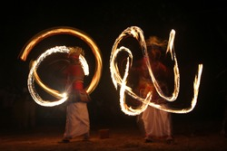 Light painting of Sri lankan traditional dancers with fire on hands