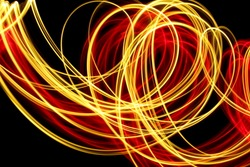 Light painting photography, gold and red swirl and loop pattern, long exposure photo against a black background