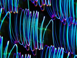 light painting photography, waves of vibrant color against a black background. Long exposure photo of vibrant fairy lights in abstract. abstract color wallpaper