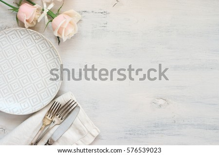 Light pastel colored tableware set: plate, vintage silverware on napkin and delicate pink roses on rustic shabby wooden background with copy space. Top view.