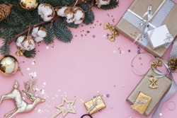 Light pink Christmas, New Year background with sequins, gifts, a branch of fir and cotton.